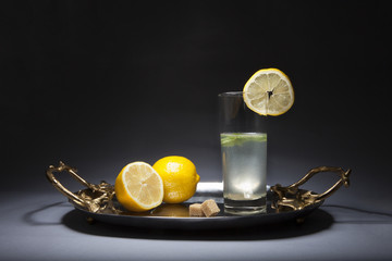 Glass of lemonade on silver tray with golden handles