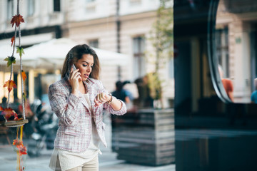 Young businesswoman talking on the phone on street
