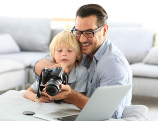 Man with little boy playing with reflex camera