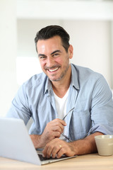 Portrait of mature man working at home with laptop