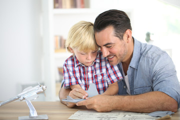 Father and kid making a plane model