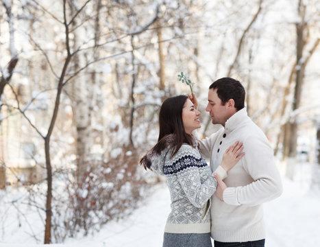 Happy young couple under mistletoe having fun