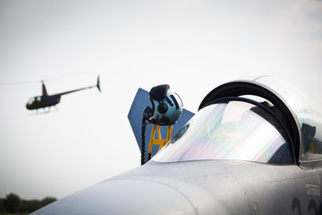 Detail of military fighter/interceptor/jetplane cockpit with pilot's oxygen mask and helmet, ready to take off in case of terrorist attack (helicopter in background, colorful image)