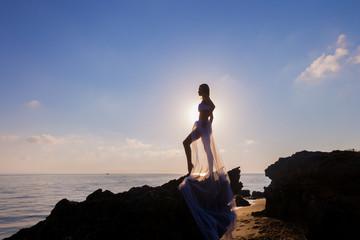 Woman enjoying freedom feeling happy at beach at sunset.