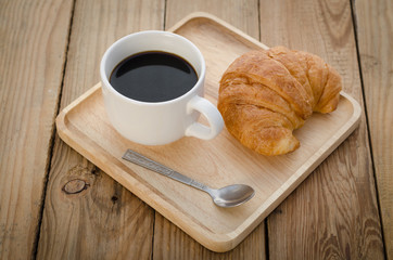 Coffee with croissants on the wooden floor.