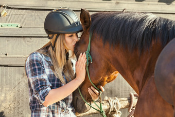 Beautiful young woman kissing her horse