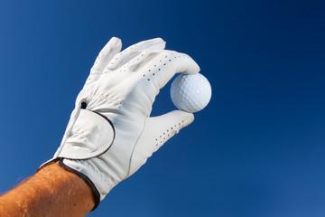 Foto op Plexiglas Golf Hand wearing golf glove holding a white golf ball