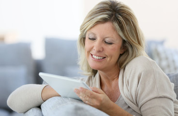 Mature woman sending email with tablet