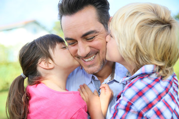 Portrait of kids giving a kiss to their daddy