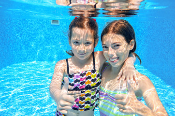 Happy active kids swim in pool and play underwater
