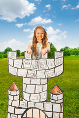 Happy beautiful girl stands on top of drawn tower