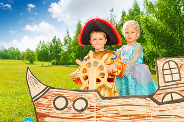 Boy as pirate holds helm and princess girl