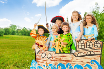Happy kids in different costumes stand on ship