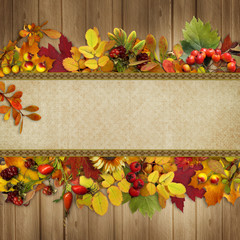 Border of autumn leaves and berries on a wooden background