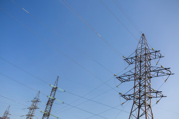 High voltage power lines on blue sky background