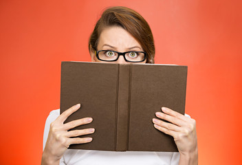 headshot woman with glasses hiding face behind book monitoring