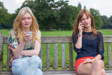 Two girls on bench in park calling mobile