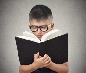 child with glasses reading book isolated grey background