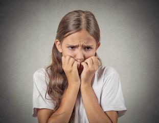 Headshot scared, shy teenager girl biting fingernails
