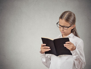 child with glasses reading book grey wall background