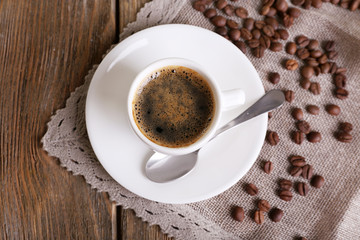 Cup of coffee with milk and coffee beans