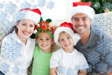 Happy family with christmas hats sitting on the sofa