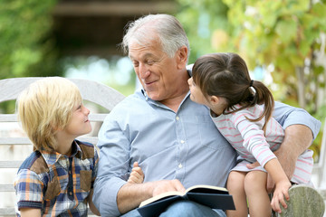 Senior man reading book with grandkids