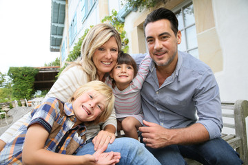 Family of four sitting in front of house