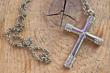 Silver christian cross with small diamonds on wooden background