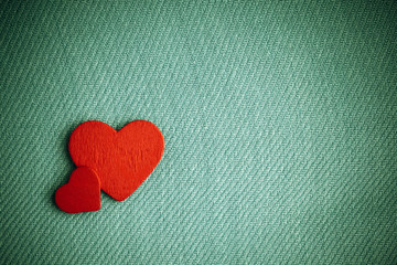 Red wooden decorative hearts on green cloth background.