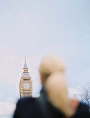 A woman looking up at Big Ben, The Elizabeth Tower at the Houses of Parliament in London.