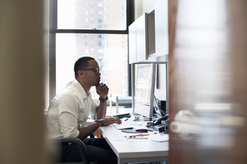 A man working in an office seated at a desk. Looking at a computer screen.