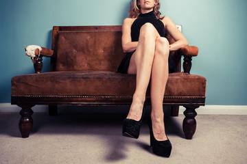 Sexy woman in heels on sofa