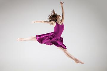Young ballet dancer wearing purple dress over grey