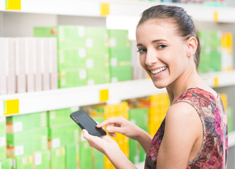 Woman with mobile at supermarket