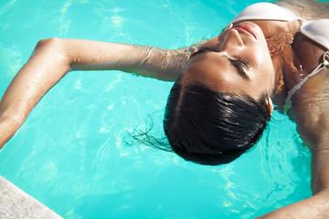 woman in white bikini enjoying in swimming pool.