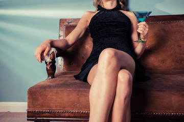 Elegant woman sitting on sofa with cocktail