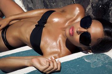 Beautiful woman in bikini and black sunglasses.