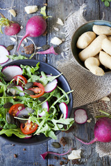 rocket salad on bowl with radish, tomatoes, seed,  bread sticks