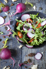 rocket salad on bowl with radish, tomatoes and seeds