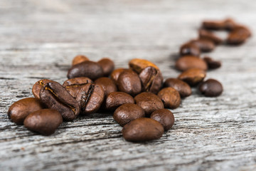 close up of coffee beans  on wooden background.