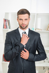 Waist-up portrait of handsome businessman with strong and confid