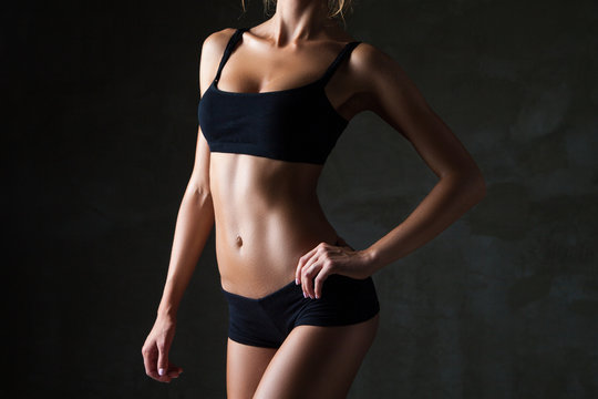 Slim woman's body  over dark grey background