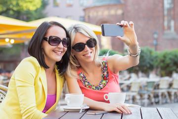 Two beautiful women taking selfie photo in cafe