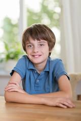 lächelnder junge sitzt zuhause am tisch