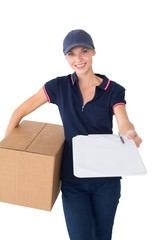 Delivery woman holding cardboard box and clipboard