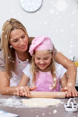 Mother and daughter baking biscuits in the kitchen