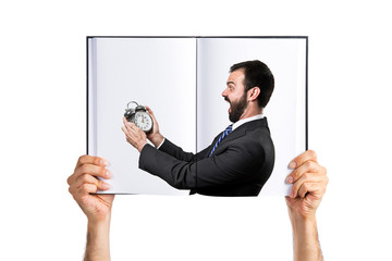 Young businessman holding an antique clock printed on book
