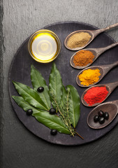 Spices, herbs and olive oil on vintage background