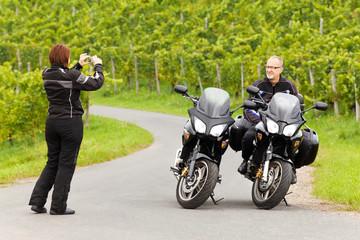 Motorradfahrerin fotografiert ihren Begleiter